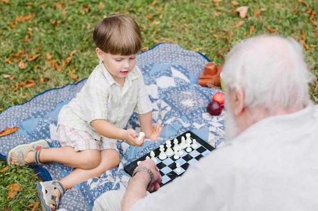 Alto ángulo abuelo y nieto jugando al ajedrez Foto gratis