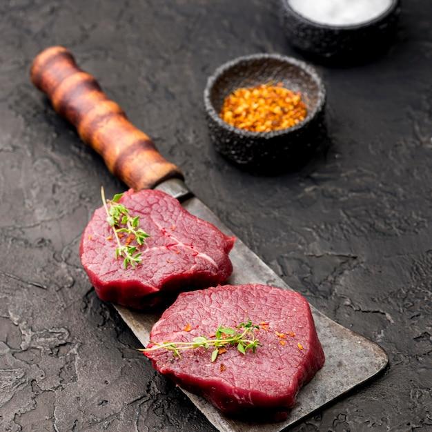 Alto ángulo de carne en cuchilla con especias y hierbas Foto gratis