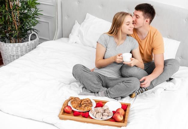 Alto ángulo feliz pareja con desayuno en la cama Foto gratis