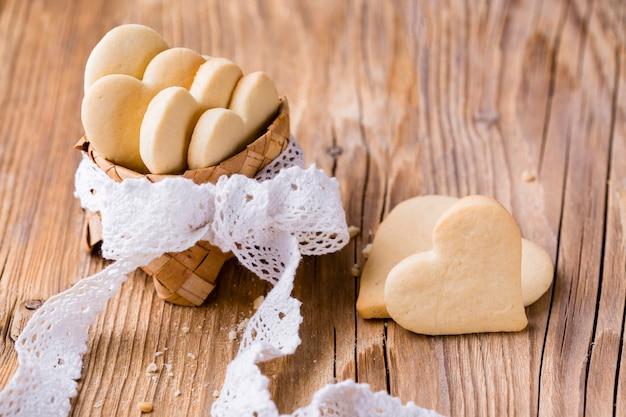 Alto ángulo de galletas en forma de corazón en la cesta con arco Foto gratis
