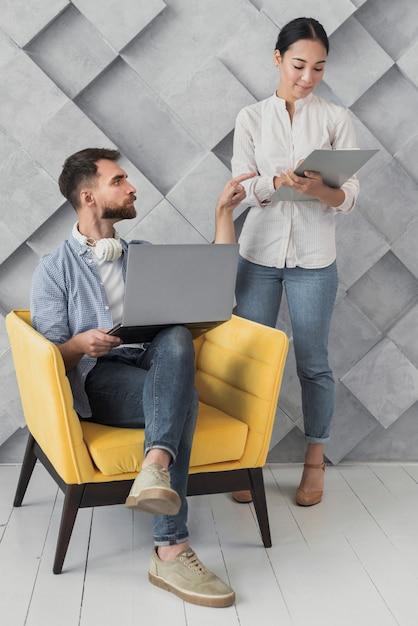 Alto ángulo masculino en silla hablando con colega Foto gratis