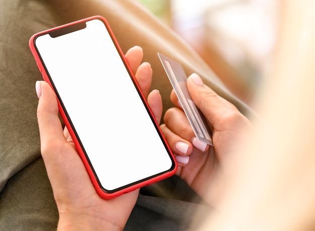 Alto ángulo de mujer sosteniendo teléfono inteligente y tarjeta de crédito para cyber monday Foto Premium