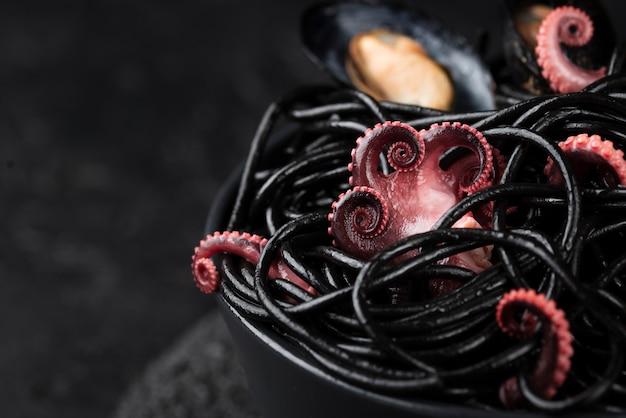 Alto ángulo de pasta negra con calamares Foto gratis