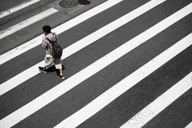 Alto ángulo de una persona en el cruce de peatones Foto gratis