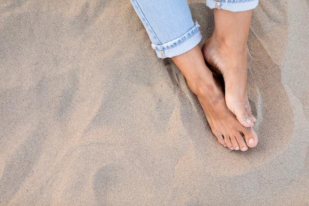 Alto ángulo de pies de mujeres en la arena de la playa Foto gratis