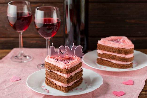 Alto ángulo de rebanadas de pastel en forma de corazón con copas de vino Foto gratis