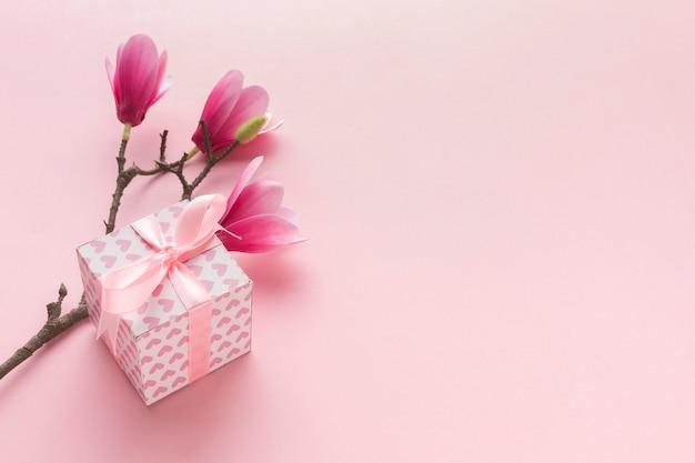 Alto ángulo de regalo rosa con magnolia Foto gratis