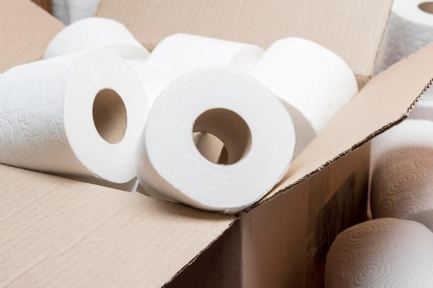 Alto ángulo de rollos de papel higiénico en caja Foto gratis