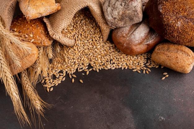 Alto ángulo de semillas de trigo que se derraman de la bolsa de yute Foto gratis