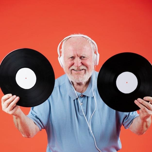 Alto ángulo senior con discos de música Foto gratis