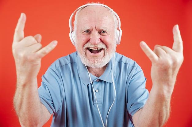 Alto ángulo senior disfrutando de la música Foto gratis