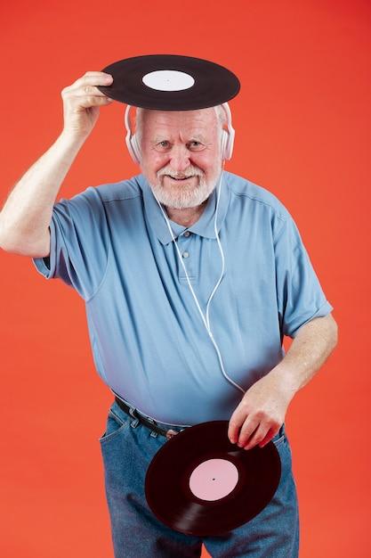 Alto ángulo senior jugando con discos de música Foto gratis