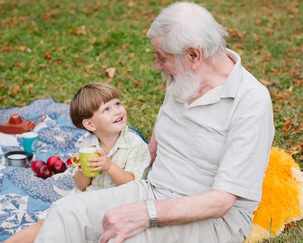 Alto ángulo sonriente nieto mirando al abuelo Foto gratis
