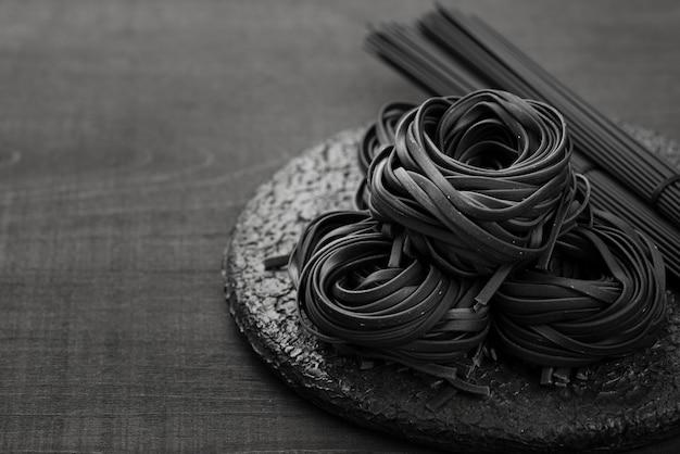 Alto ángulo de tagliatelle negro en plato con espagueti Foto gratis