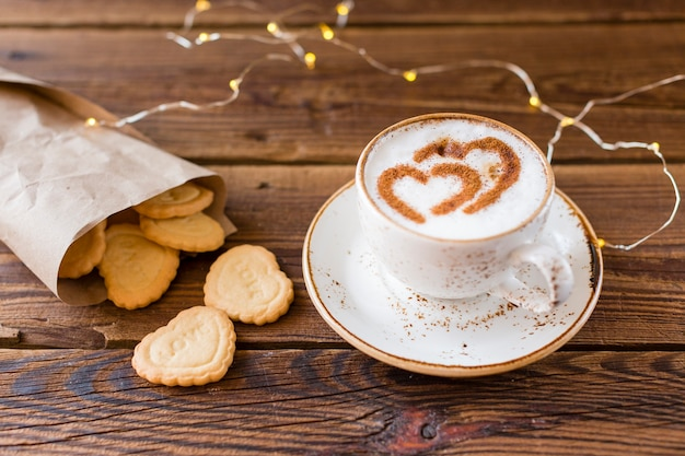 Alto ángulo de taza de café y galletas en forma de corazón. Foto gratis