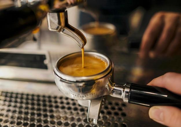 Alto ángulo de la taza de la máquina de café sostenida por barista Foto Premium