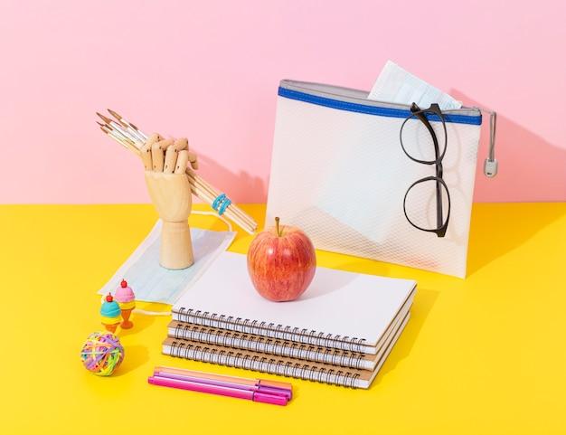 Alto ángulo de útiles escolares con cuadernos y manzana Foto Premium