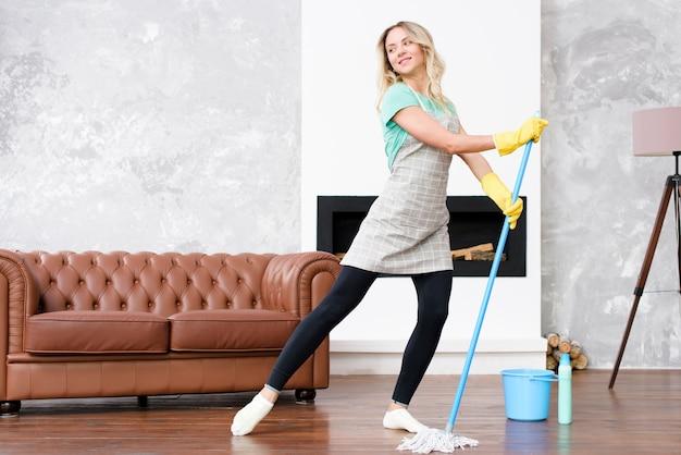 Ama de casa mujer vistiendo delantal bailando con un trapeador mientras realiza las tareas domésticas Foto gratis