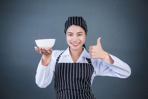 Una ama de casa sosteniendo un plato vacío con comida. Foto gratis