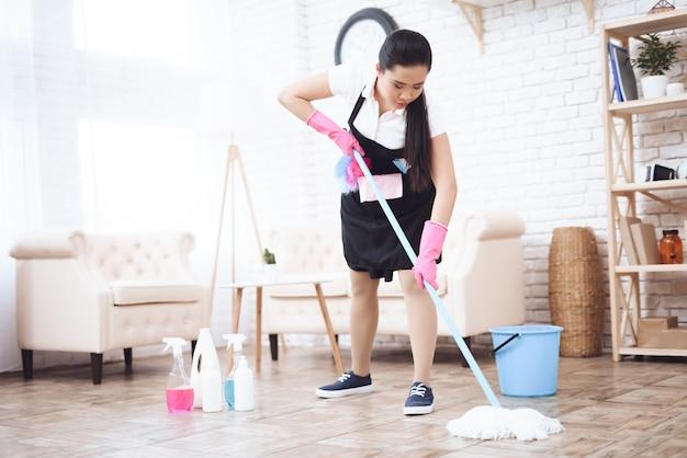 Ama de llaves limpiando el piso con un trapeador y detergentes. Foto Premium