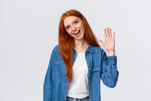 Amable, alegre y extrovertida guapa pelirroja agitando la palma de la mano, saludando Foto Premium