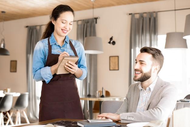 Amable camarera tomando orden del cliente Foto Premium