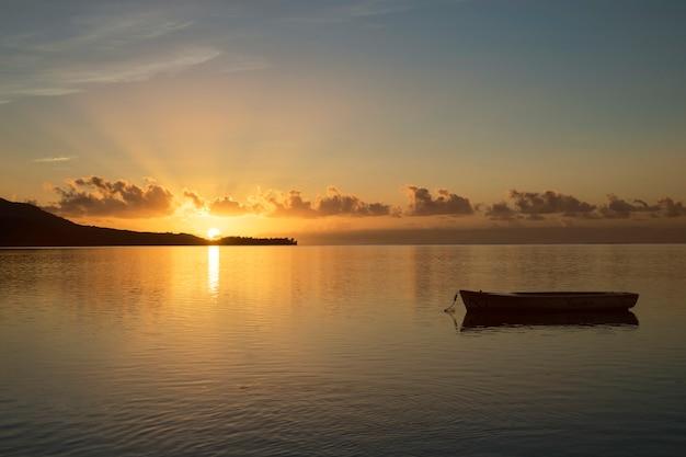 Amanecer en mauricio con el sol en el fondo y un barco de pesca en primer plano Foto Premium
