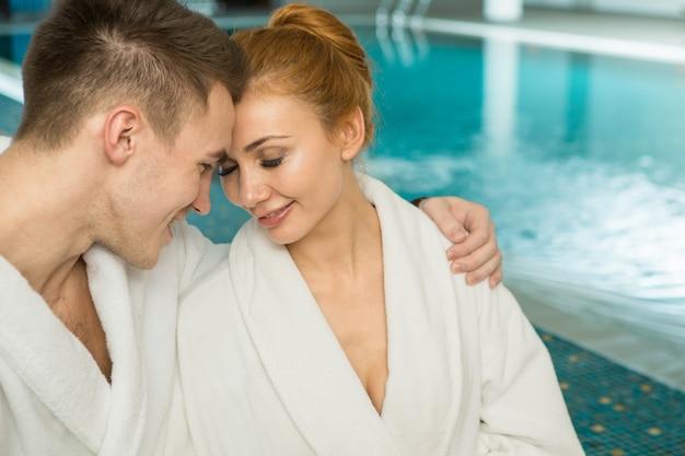 Amante joven pareja en batas de baño relajantes juntos en la piscina Foto Premium
