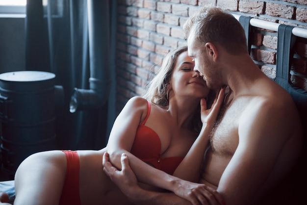Amantes jóvenes jugando juntos en la cama, vistiendo lencería sexy en una habitación de hotel. Foto gratis