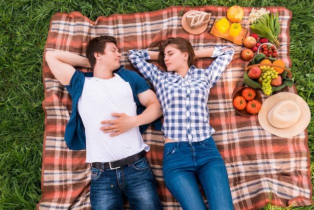Amantes jovenes que toman siesta en la manta afuera Foto gratis