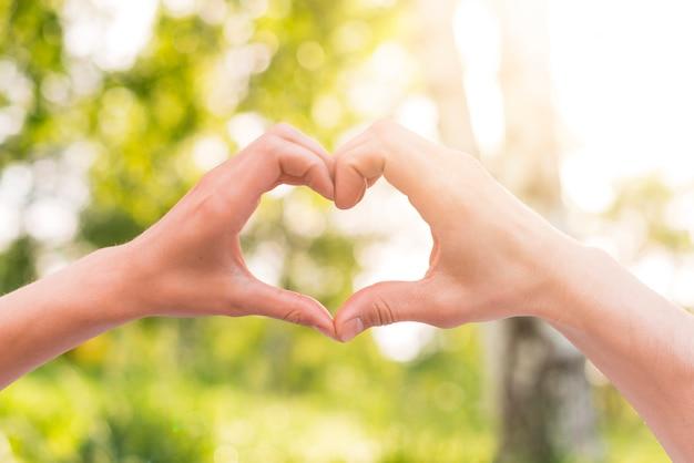 Los amantes que gesticulan el corazón firman con las manos afuera Foto gratis