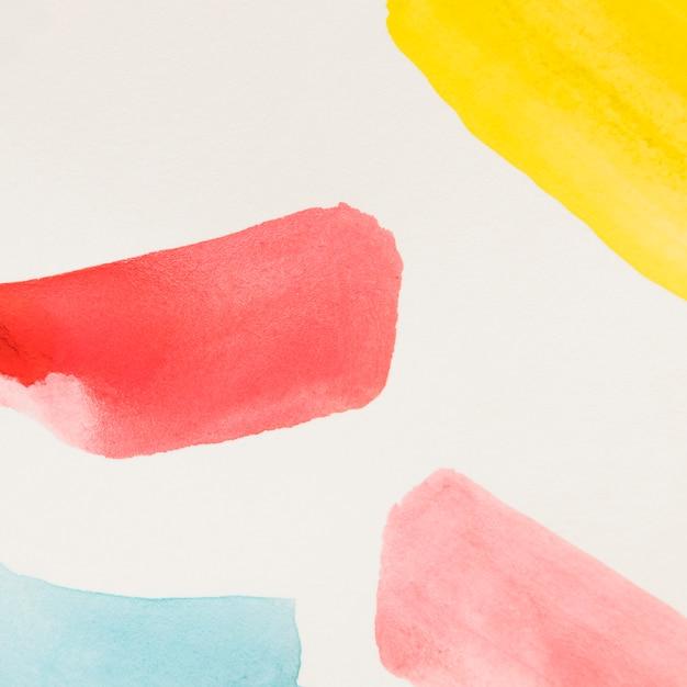 Amarillo diferente trazo de pincel rojo y azul de acuarela sobre fondo blanco Foto gratis