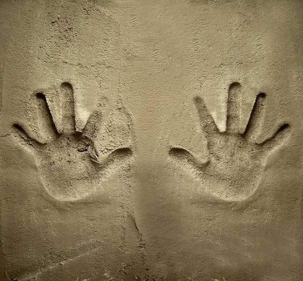 Ambas manos se imprimen en la pared de cemento mortero Foto Premium