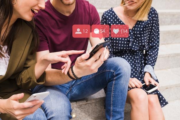 Una amiga apuntando al hombre usando iconos de notificación de red social sobre el móvil Foto Premium