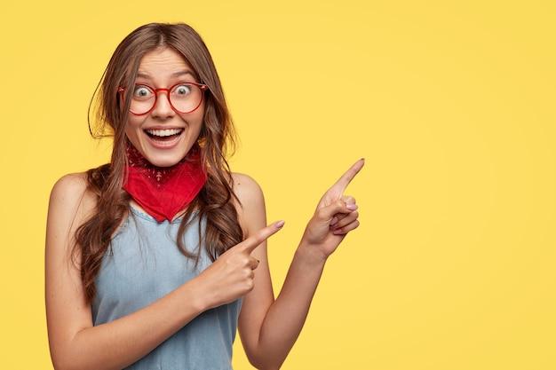 La amigable y despreocupada asistente de tienda apunta a la derecha, tiene una sonrisa en el tablero, anuncia un nuevo atuendo con grandes descuentos, usa lentes transparentes, modelos contra la pared amarilla con espacio para copiar el lema Foto gratis