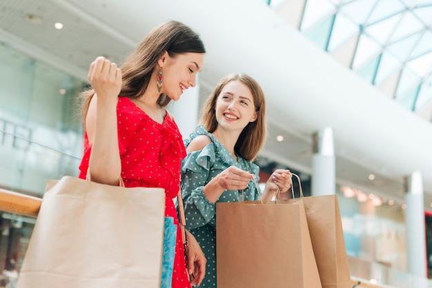 Amigas de bajo ángulo en el centro comercial Foto gratis