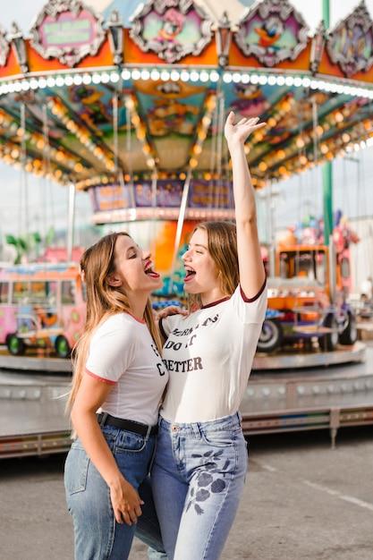 Amigas felices divirtiéndose en el parque de atracciones Foto gratis