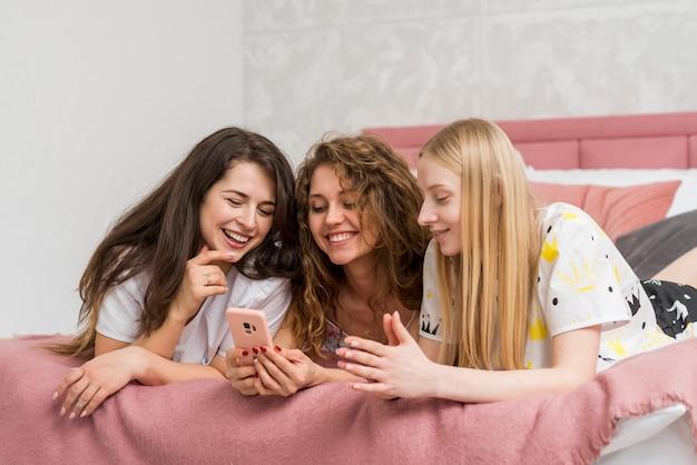 Amigas en fiesta de pijamas mirando móvil Foto gratis