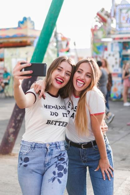Amigas jóvenes haciendo un selfie en el parque de atracciones Foto gratis