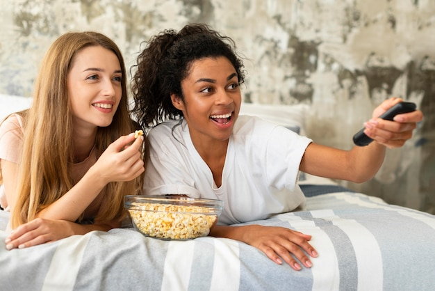 Amigas sonrientes viendo la televisión en la cama Foto Premium