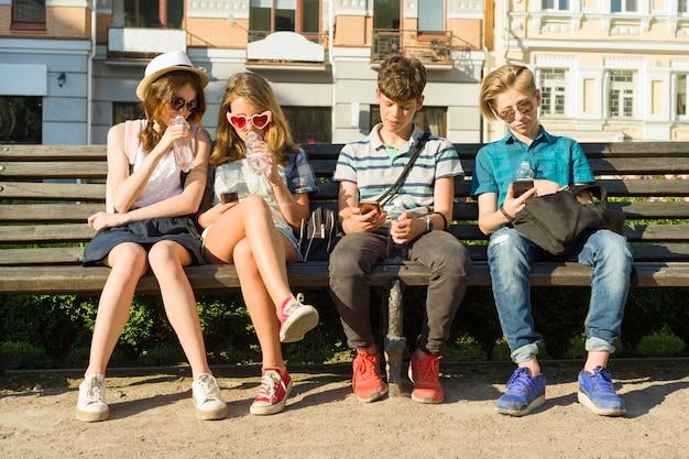 Amigos adolescentes niña y niño sentado en el banco Foto Premium