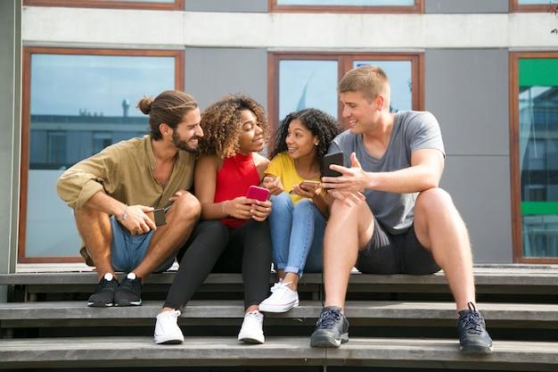 Amigos alegres felices leyendo noticias en las pantallas del teléfono Foto gratis