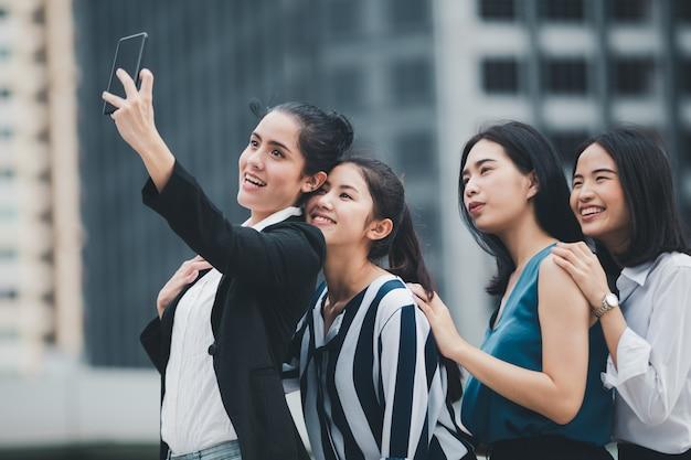 Amigos asiáticos de la empresaria de la forma de vida que sonríen y que se divierten caminando el selfie en la ciudad Foto Premium