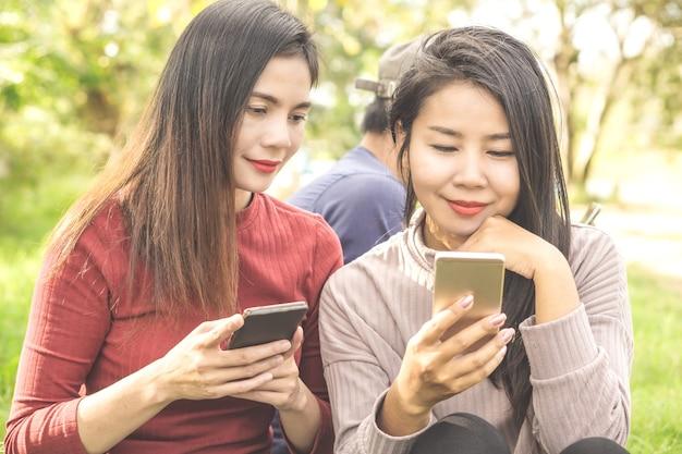 Amigos asiáticos de la mujer que se sientan en un parque usando el teléfono elegante Foto Premium