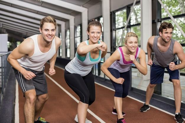 Amigos atléticos sonrientes van a comenzar a correr en la pista Foto Premium