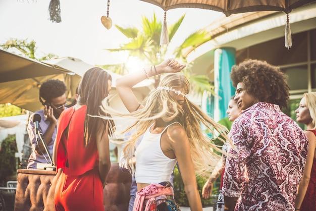 Amigos bailando en un lounge bar, con dj set Foto Premium