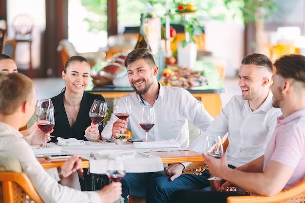 Los amigos beben vino en la terraza del restaurante. Foto Premium
