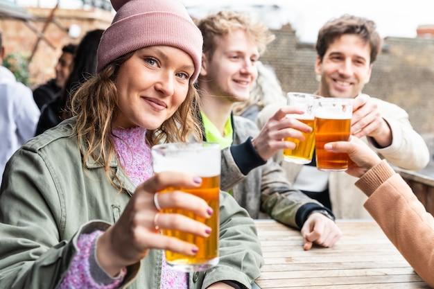 Amigos bebiendo y brindando con cerveza en el pub Foto Premium
