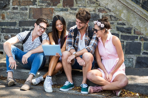 Amigos de la cadera mirando tableta y sentado en la acera Foto Premium
