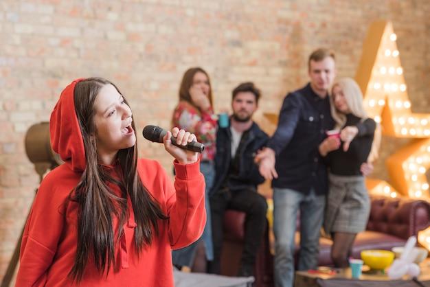 Amigos cantando al karaoke en una fiesta Foto gratis